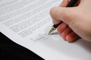 Ein Anwalt unterschreibt den Werbevertrag